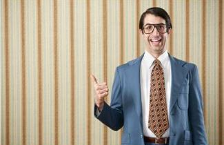 Nerdy guy wearing glasses, smiling and making a thumbs up gesture.